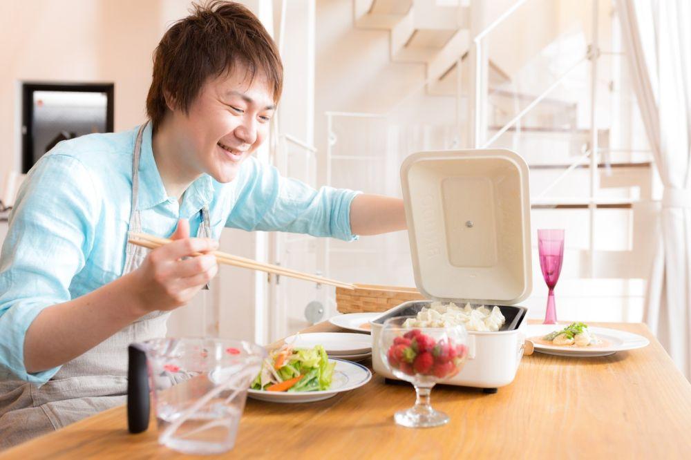 ダイニングテーブルに料理を運ぶ男性