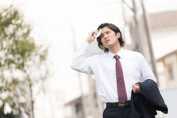 外回りで汗をかぬぐうビジネスマン