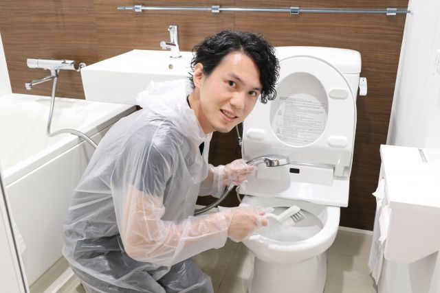 ウォシュレット付きトイレを掃除する男性